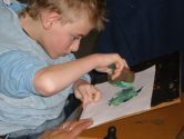 Marshall is using a stencil and sponge to make the shape of a bird