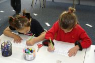 Aaliyah and Jennifer sit together and practise writing 'u'