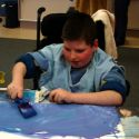 Lucas covers the canvas with paint using a sponge brush