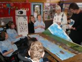 The children decide where each image will be placed on the large canvas