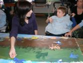 Sarah and Charlie work together to place Charlie's bird image on the large canvas